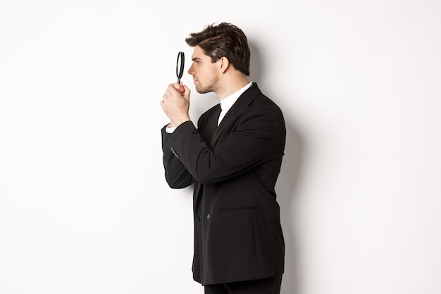 Profile shot of handsome businessman in black suit, looking through magnifying glass and searching for something, standing over white background.