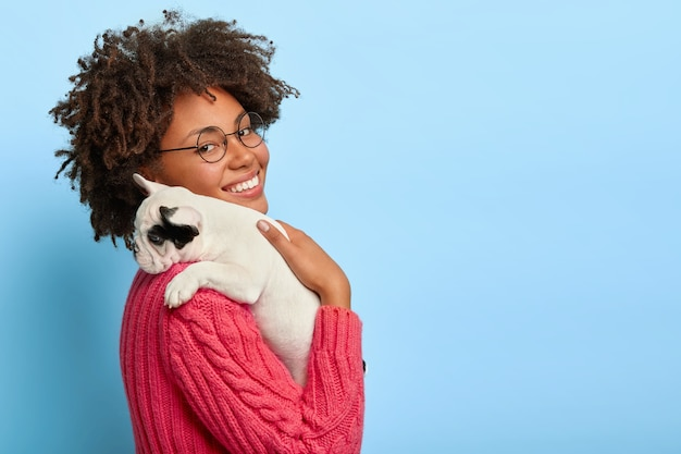 Profile shot of happy dark skinned woman carries little pedigree puppy on shoulder, plays with her pet during spare time, going to park, wears glasses and sweater. cute moments.