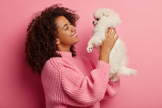 Profile shot of happy smiling woman raises miniature dog in both hands, looks with pleasure and smile, found stray pet, dressed in knitted jumper, poses over pink wall, expresses positive emotions