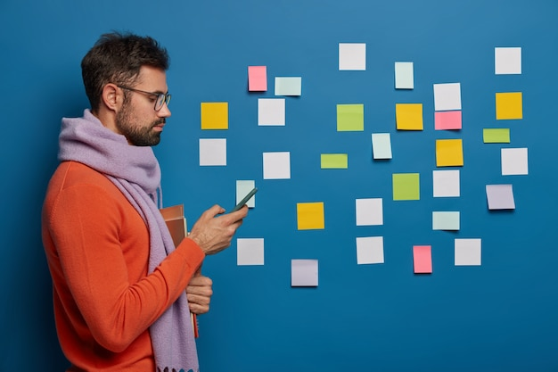 Profile shot of male business professional dressed in warm clothing, uses modern mobile phone for sending text messages, holds textbooks, sticking colorful papers in background