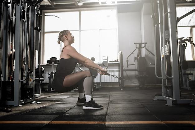 Снимок профиля спортсменки, сидящей на корточках в тренажерном зале кроссовера