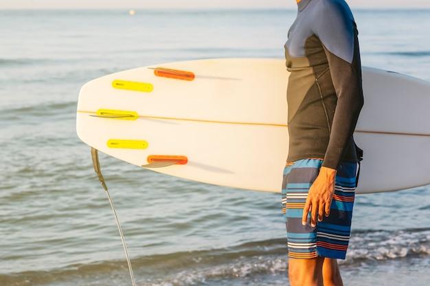 Выстрел в профиль молодого человека, стоящего с доской для серфинга на пляже.