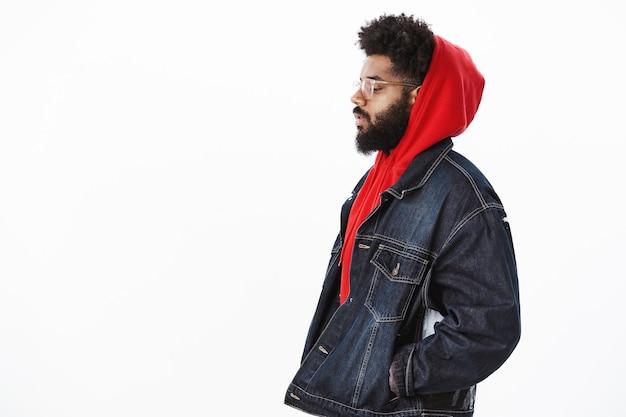 赤いパーカーの上にデニムジャケットを着た夢のような思慮深いハンサムなスタイリッシュなアフリカ系アメリカ人の男のプロフィールショット、歩いて考えているようにポケットに手をつないで見下ろし、重要な決定を下す