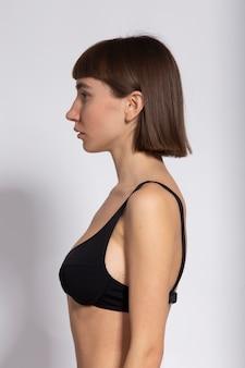 검은 브래지어에 흰색 절연 귀 뒤에 그녀의 머리를 가진 모델의 프로필 샷