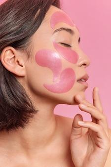 부드러운 갈색 머리 여성의 프로필 사진은 얼굴 터치 턱에 패치를 적용하고 분홍색 벽에 셔츠를 입지 않은 채 실내에서 눈을 감고 있습니다.