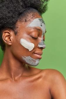 얼굴 피부에 대해 토플리스로 관리하는 여성의 프로필 사진은 회춘을 위해 영양이 풍부한 점토 마스크를 적용하여 녹색 벽에 격리된 주름 방지 절차를 수행합니다