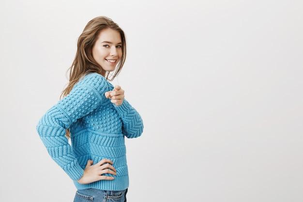 カメラに背を向けて、喜んで笑顔で指を指している女性のプロフィールショット