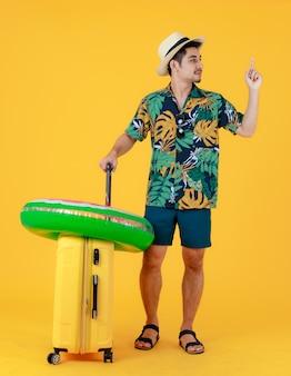 프로필 사진, 화려한 하와이안 셔츠를 입은 젊은 아시아 남성이 검지 손가락을 들고 노란색 가방을 당깁니다. 노란색 배경에 전신 스튜디오 초상화입니다. 행복한 여름 휴가 여행 컨셉입니다.