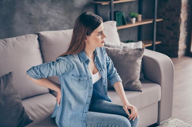 プロフィール側欲求不満の女の子はソファに座るタッチハンドバックは痛みを感じる