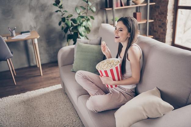 プロフィール側面白い女の子は家にいる時計コメディショーはポップコーンを食べる