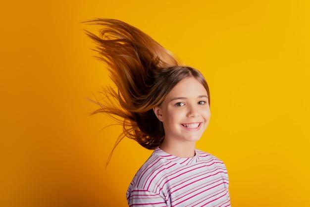Сторона профиля счастливая маленькая девочка со светлыми волосами, летящими на желтом фоне