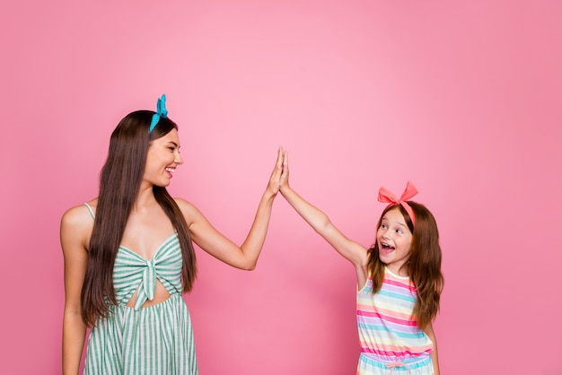 Profile side photo of cheerful siblings giving high five screaming wearing bright headbands dress skirt isolated over pink background