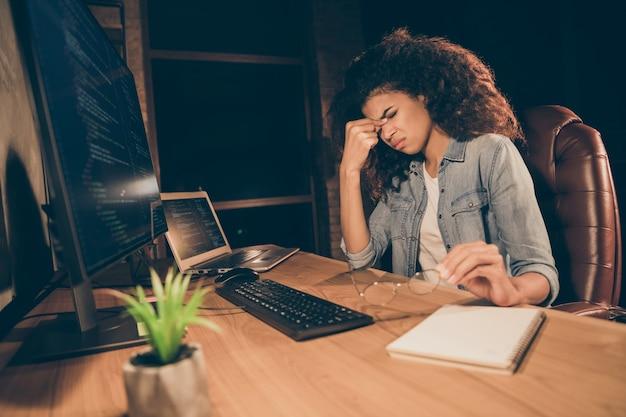 Фото сбоку профиля подавленная подчеркнутая афро-американская девушка работает сверхурочно за компьютером