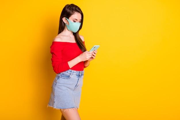 プロフィールサイド写真フォーカスされた医療マスクの女の子は、covid検疫トレンドを使用しますスマートフォンのコピースペースを着用します赤いトップデニムジーンズショートミニスカート孤立した明るい輝きの色の背景