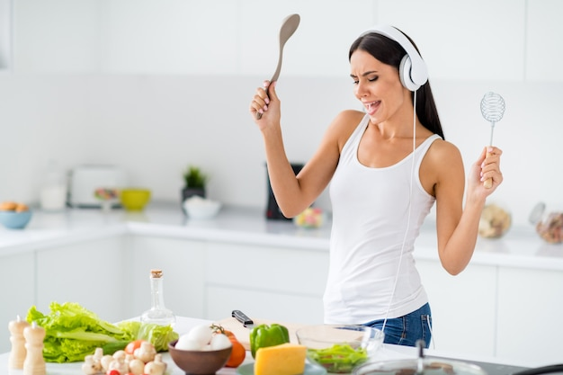 Profile side photo of funny funky house wife wearing headset sing stereo volume song listen music cook tasty healthcare supper in white kitchen house  having vegetables eggs cheese tomato