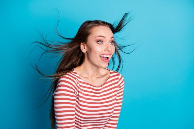 驚いたポジティブな女性のプロフィールサイド写真感動空気風吹髪型髪型悲鳴を楽しむ青い色の背景の上に分離されたスタイリッシュなトレンディな服を着て楽しむ