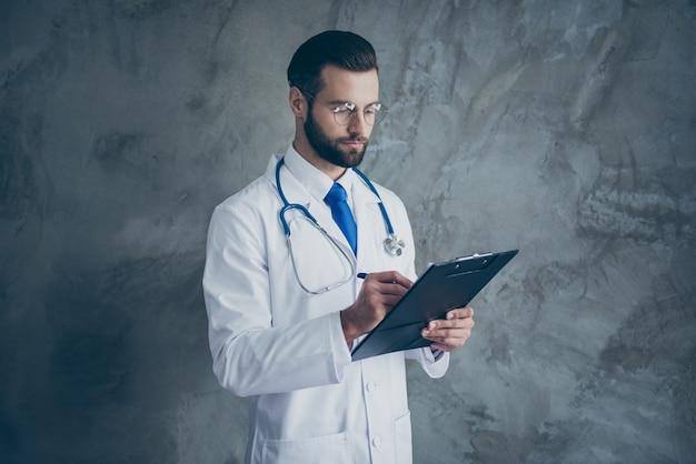 집중된 외과 의사 남자의 프로필 측면 사진은 환자의 불만이 그의 클립 보드에 쓰기를 듣고 회색 벽 위에 절연 흰색 의료 코트를 착용