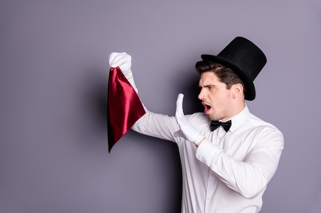 Фото сбоку в профиле фанкового волшебника-фокусника, держащего красную салфетку, скажем, заклинания хотят показать фокус носить белую стильную рубашку с галстуком-бабочкой, изолированную над серой стеной Premium Фотографии