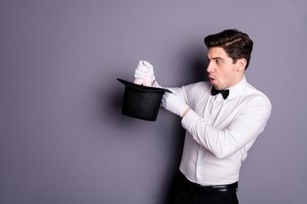 Фотография сбоку в профиле фанкового волшебника-волшебника, впечатленного чудом, делающим фокус, удерживайте заячьи уши, которые он вытаскивает из цилиндрической шляпы, в белой рубашке, с черным бантом, изолированной на серой стене