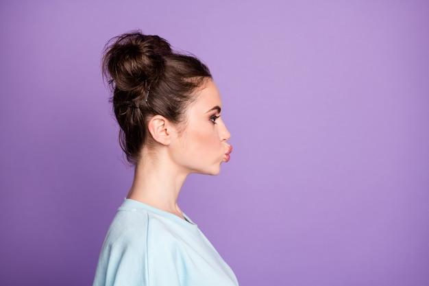 ゴージャスなかわいい女の子の若者のプロフィールサイド写真は、紫色の背景の上に分離されたカジュアルなスタイルの服を着て彼女のボーイフレンドに空気のキスを送信します