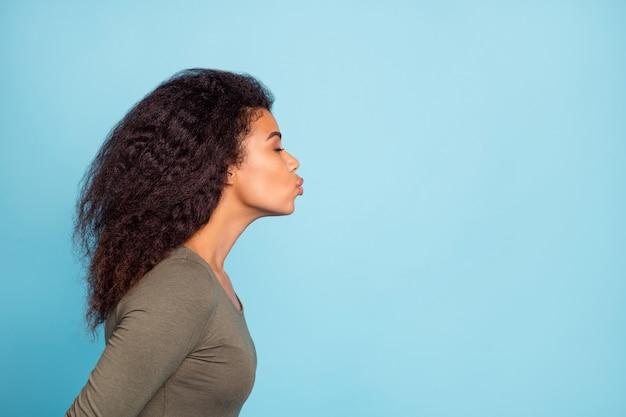 Фото сбоку профиля радостной романтической афроамериканской девушки на свидании, отправляющей воздушные поцелуи своему парню, одежда copyspace, пуловер в повседневном стиле, изолированный на стене синего цвета