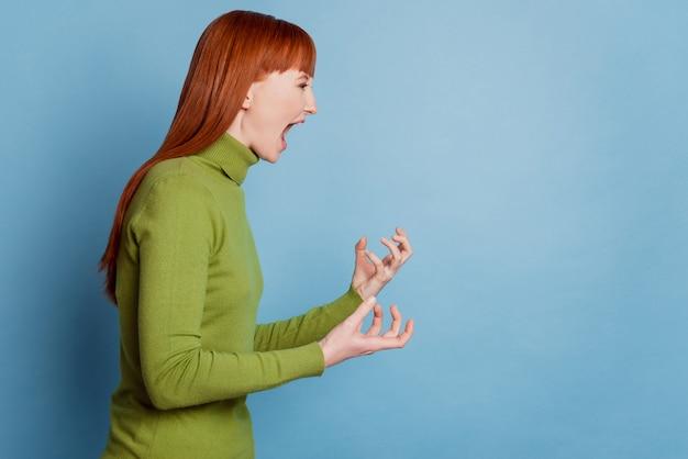 Фото сбоку профиля сумасшедшей женщины, кричащей пустое пространство, изолированное на синем фоне