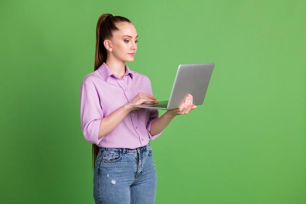 집중하는 ceo 여성의 프로필 측면 사진 원격 노트북에는 소셜 네트워킹 wi-fi 통신이 녹색 배경 위에 격리된 라일락 바이올렛을 착용하고 있습니다.