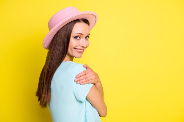 ポジティブな素敵な女の子の横顔の横の写真は、自分自身を抱きしめ、快適で居心地の良い抱きしめるコピースペースを楽しんでください鮮やかな色の背景の上に隔離された格好良い服を着てください