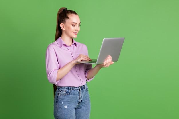 긍정적인 관리자 소녀 작업 원격 노트북의 프로필 측면 사진에는 wi-fi 연결 소셜 네트워킹 통신이 있는 라일락 바이올렛 데님 청바지가 녹색 배경에 격리되어 있습니다.
