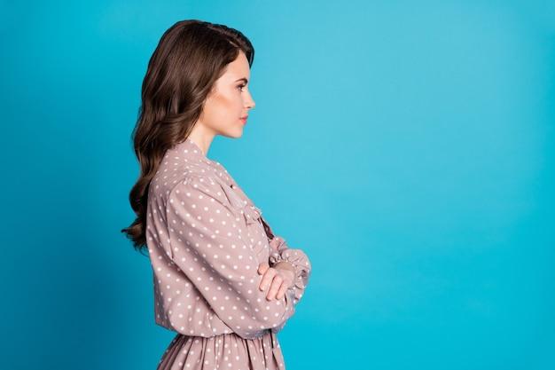 Фото сбоку профиля надежной великолепной девушки босса скрестив руки взгляд copyspace слушать ее коллеги ошейники решение носить одежду в горошек, изолированную на синем цветном фоне