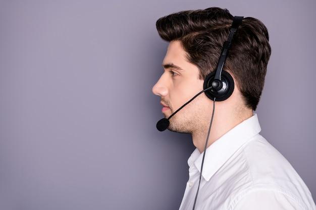 심각한 자신감 멋진 고객 지원 작업자 모양 copyspace의 프로필 측면 사진은 이어폰이 고객이 회색 벽 위에 고립 된 공식적인 흰색 셔츠를 입도록 도와줍니다.