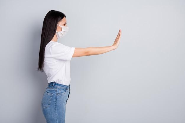 Фото сбоку профиля строгой девушки, избегающей заражения вирусом короны, больные люди держат жест рукой стоп, носить медицинскую маску, футболка, джинсовые джинсы, изолированные на сером цветном фоне