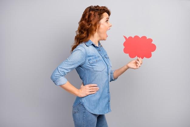 驚いた狂気の女性のプロフィールの側面写真は赤い紙のカードの泡を保持します印象的な叫び声信じられないほどの信じられないほどのプロモーションは灰色の壁の上に分離されたモダンな衣装を着ます