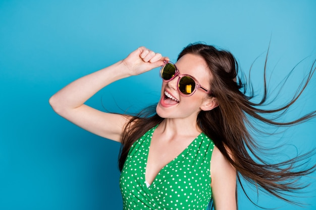 Profile side photo of pretty candid girl touch glasses enjoy rejoice weekend air wind blow hairstyle wear good look clothes isolated over blue color background