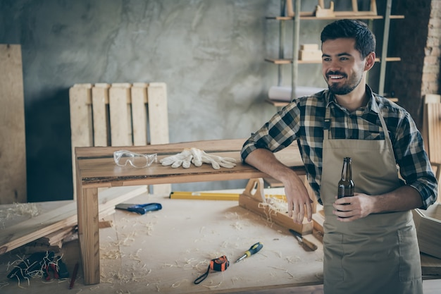 Profile side  positive cheerful worker hardwood worker complete his renovation slab table order relax rest hold bottle beer enjoy in house home garage