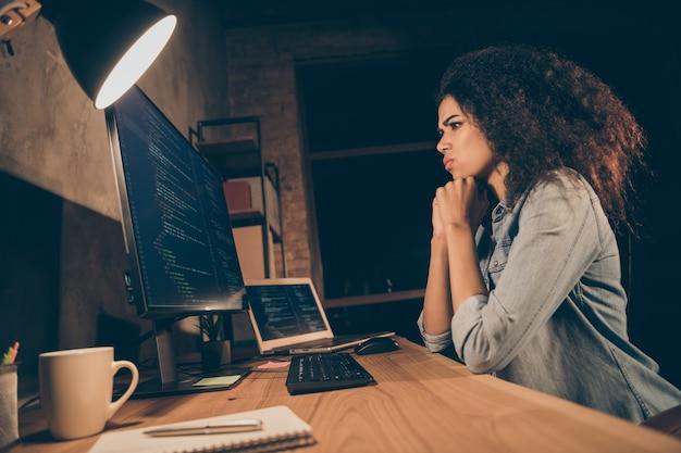 Сбоку в профиль озадаченная девушка-хакер сидит на рабочем столе и смотрит на экран компьютера