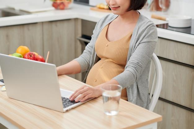 프로필 측면보기 매력적이고 진보적 인 젊은 엄마는 밝은 평면 내부 테이블 뒤에 의자에 앉아 pc 노트북을 사용