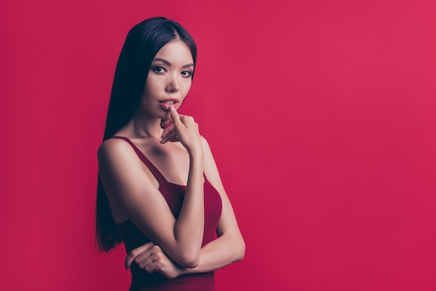 彼女が赤い壁に隔離したプロフィールの側面図魅力的な人は彼女の下唇に触れます
