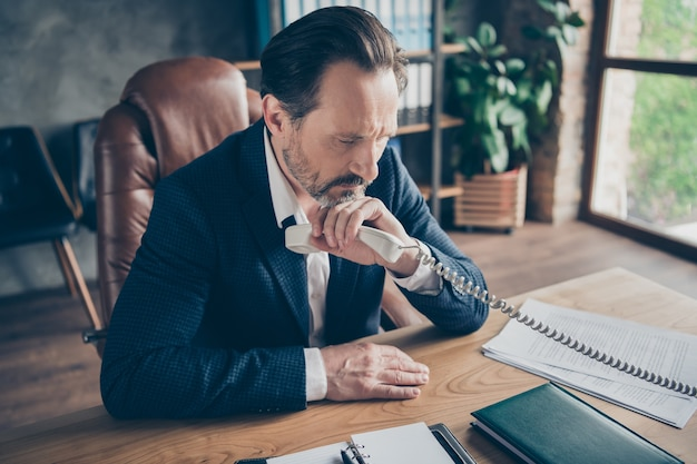 Profile side view close-up portrait of grumpy unsuccessful depressed jobless guy finance employee talking on phone find crisis solution at modern loft industrial style interior workplace workstation