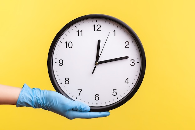 Profile side view closeup of human hand in blue surgical gloves holding analog clock.