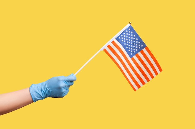 Profile side view closeup of human hand in blue surgical gloves holding usa national flag.
