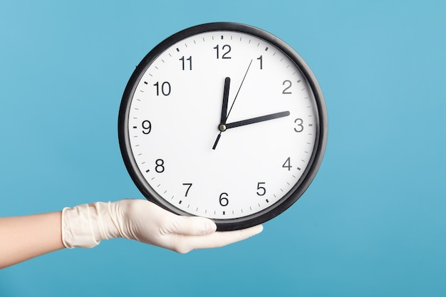 Profile side view closeup of human hand in white surgical gloves holding analog clock.