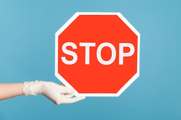 Profile side view closeup of human hand in white surgical gloves holding and showing stop sign.