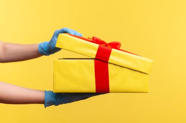 Крупный план взгляда со стороны профиля человеческой руки в синих хирургических перчатках держа и раскрывая желтую подарочную коробку.