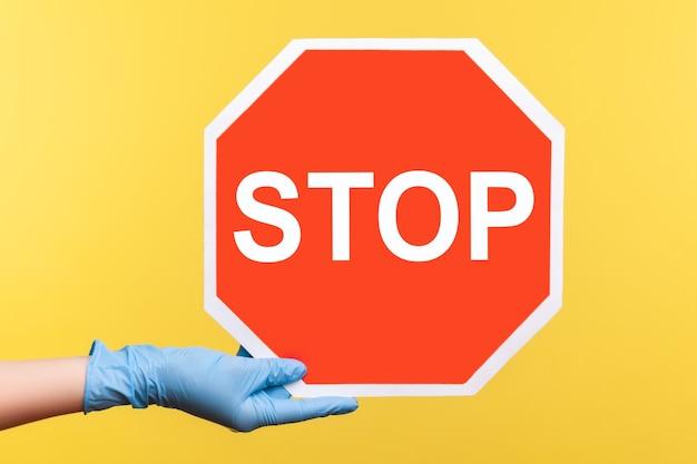 一時停止の標識を保持し、表示している青い手術用手袋で人間の手のプロファイル側面図のクローズアップ。
