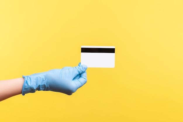 Профиль вид сбоку крупным планом человеческой руки в синих хирургических перчатках, держащей классическую кредитную карту.