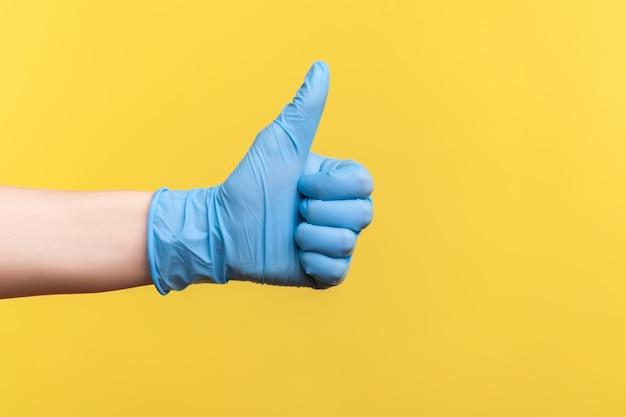 青い手術用手袋をはめた人間の手の横顔のクローズアップのように、または親指を立てて表示します。