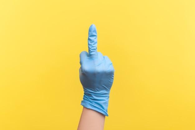 가운데 손가락을 보여주는 파란색 수술 장갑에 인간의 손의 프로필 측면 보기 근접 촬영.