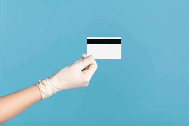 Крупный план вида сбоку профиля человеческой руки в белых хирургических перчатках, держащей классическую кредитную карту.
