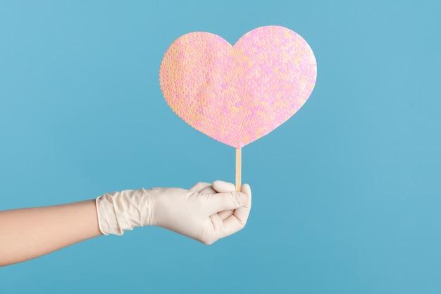 프로필 측면 보기 심장 분홍색 사랑 막대기를 들고 흰색 수술 장갑에 인간의 손의 근접 촬영.